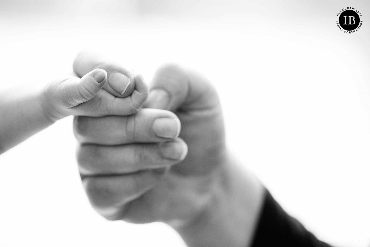 newborn baby holds mum's finger, black and white professional photo