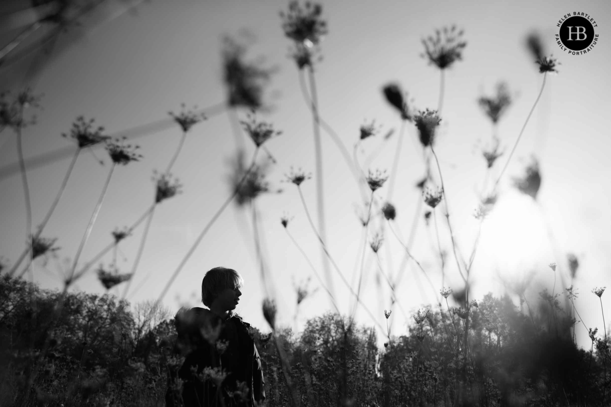 silhouette of boy among long grasses, dramatic black and white photograph