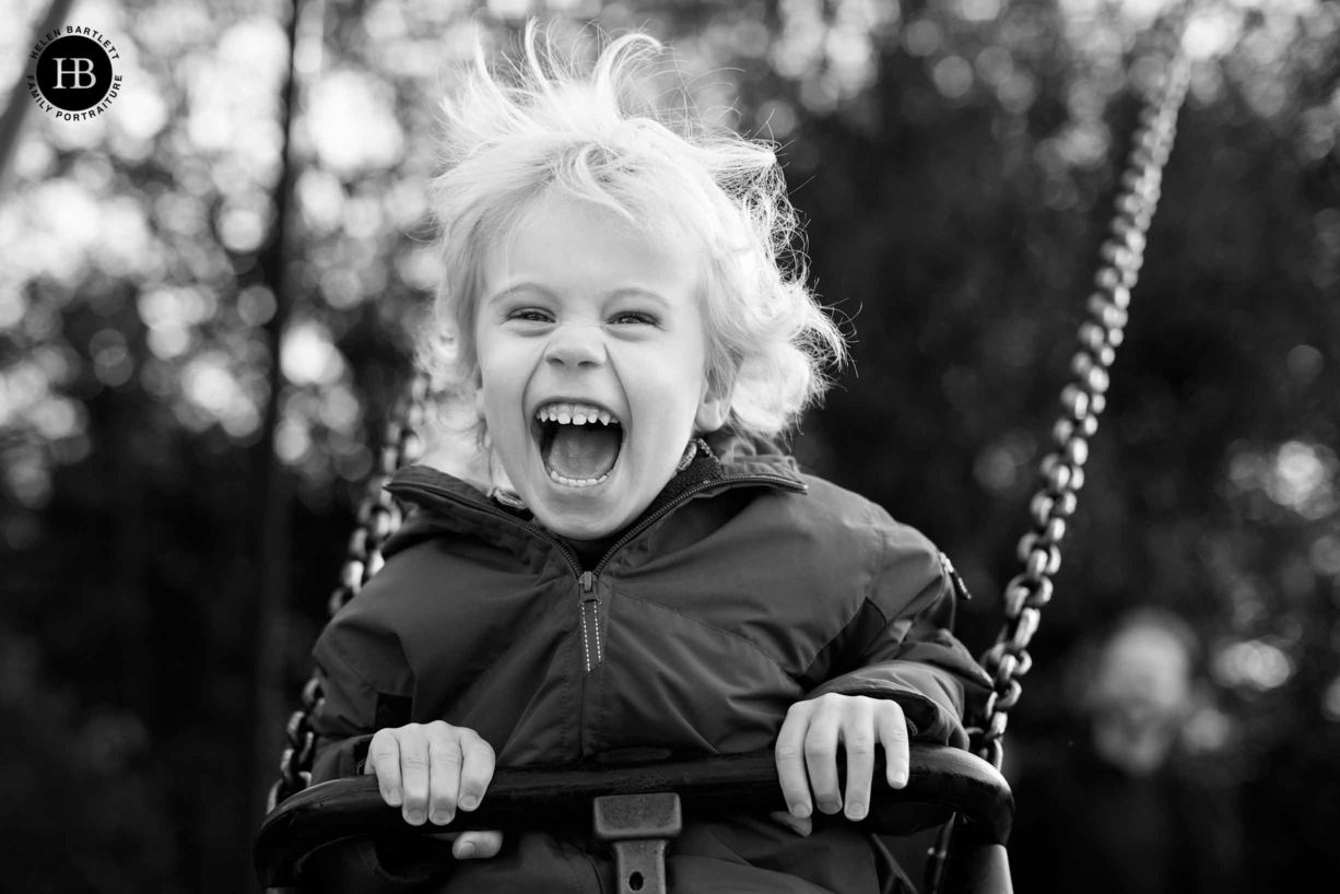 young boy laughing on a swing in Islington North London N1