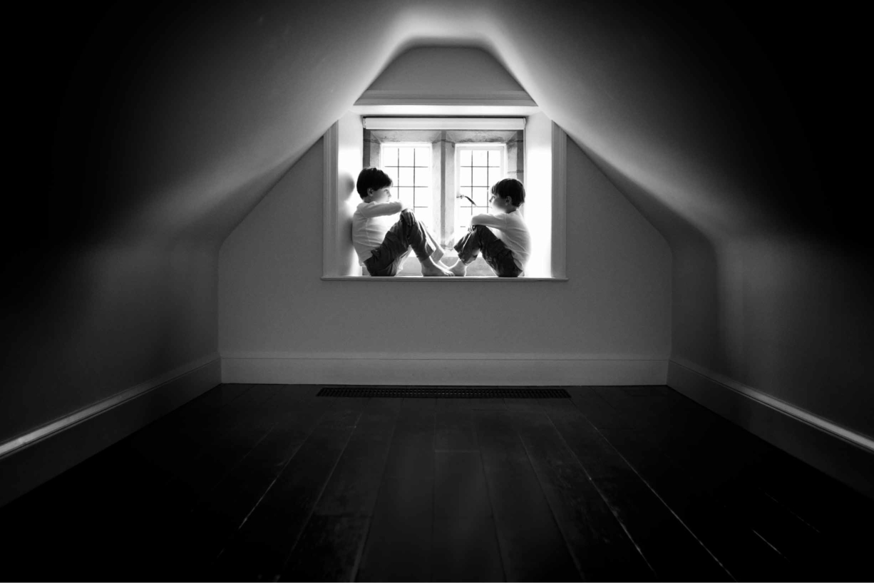 boys sit in a window in beautiful architectural nook on professional photo shoot
