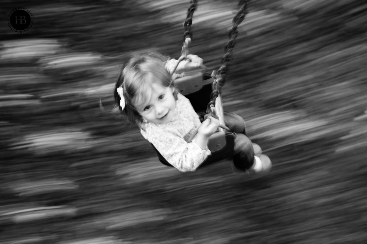 girl on a swing shot from above using panning technique during a family photography session in Islington N1