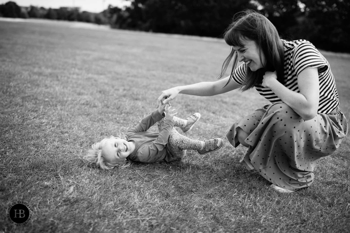 Mum tickles her daughter during a family photo shoot, both are laughing