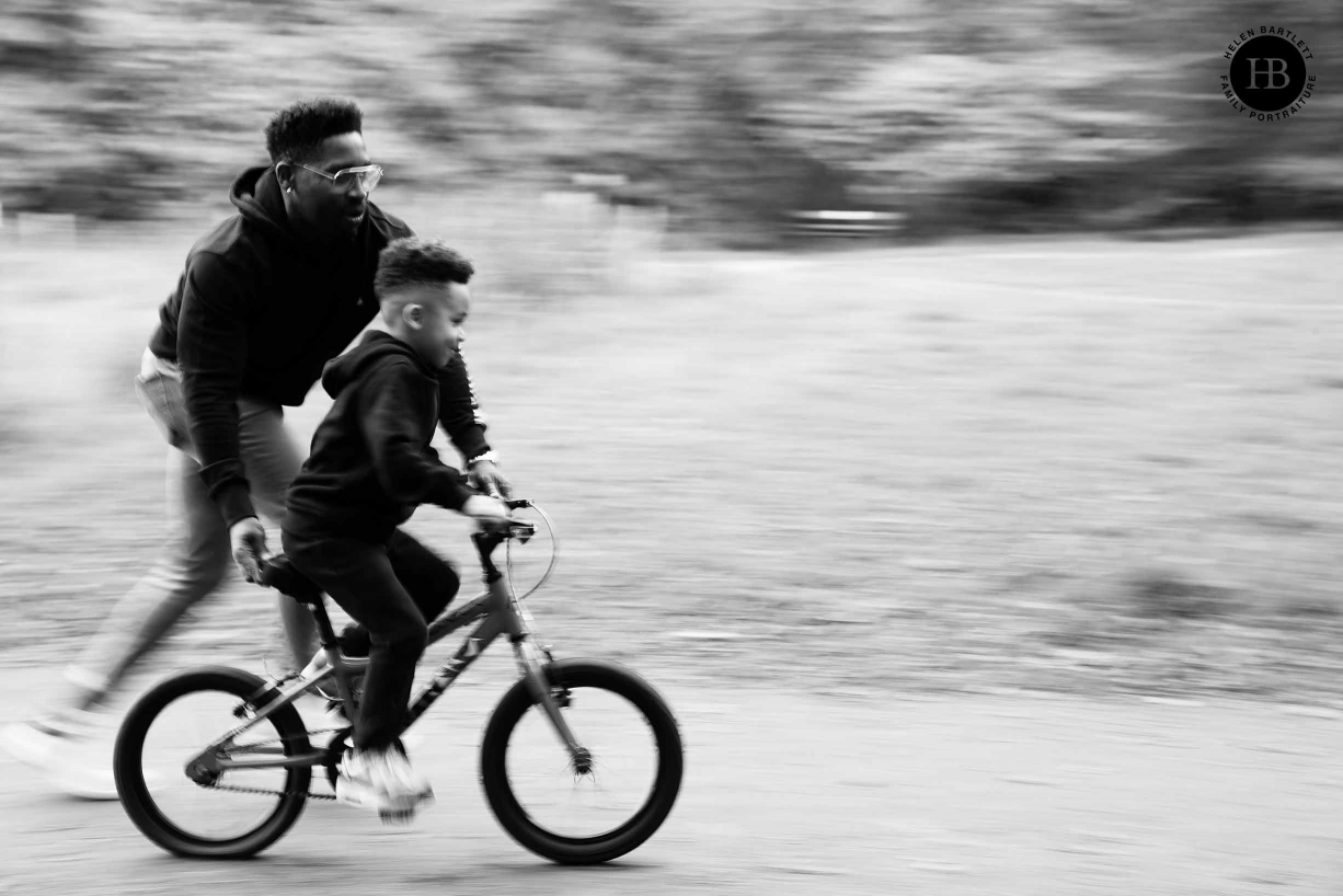 dad pushes his son on a bicycle in Greenwich Park London