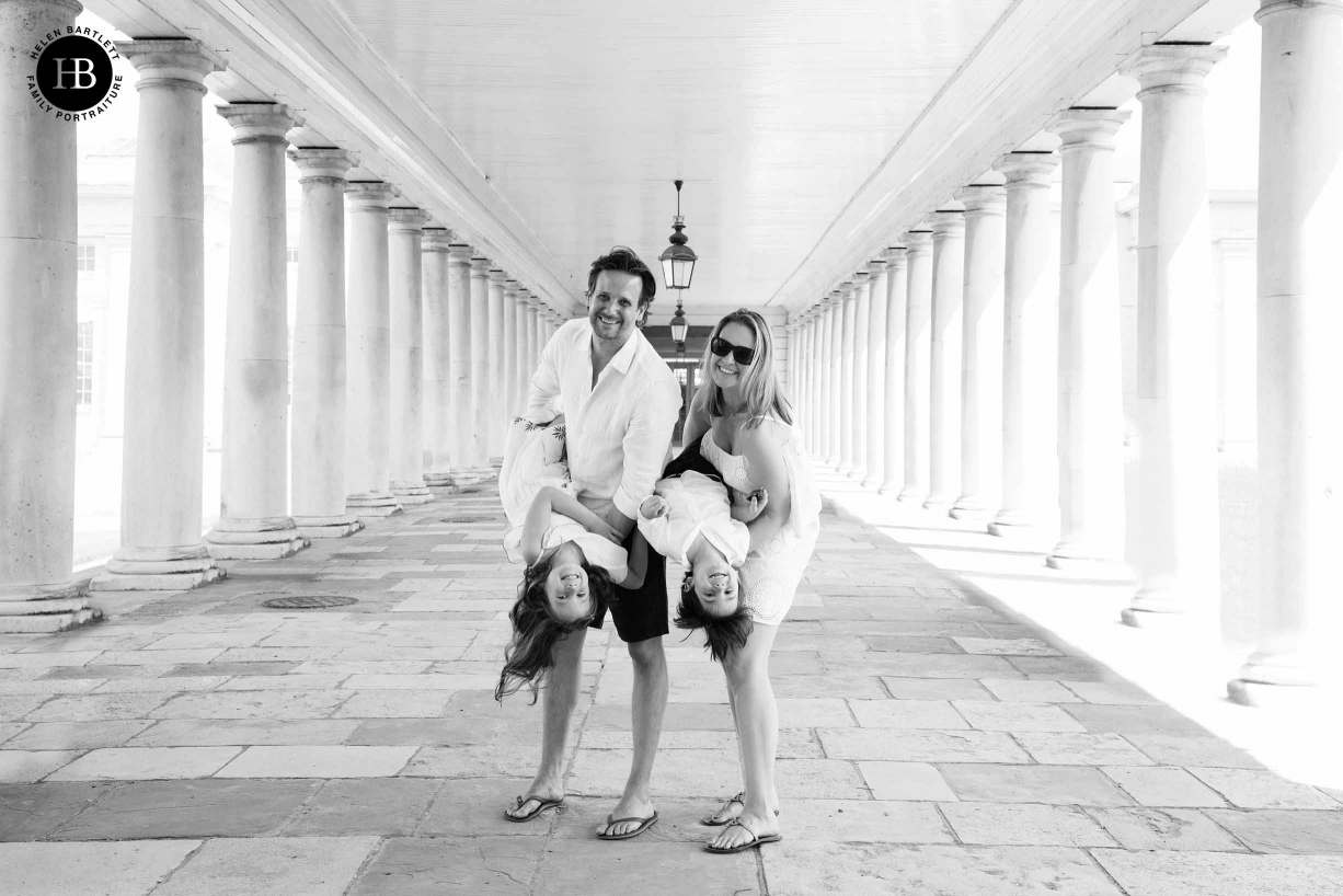 professional family photo in colonnades in Greenwich, parents hold children upside down. Everyone has fun