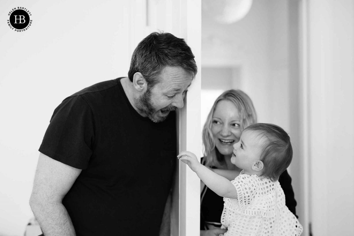 family play hide-and-seek behind a door at home in Greenwich