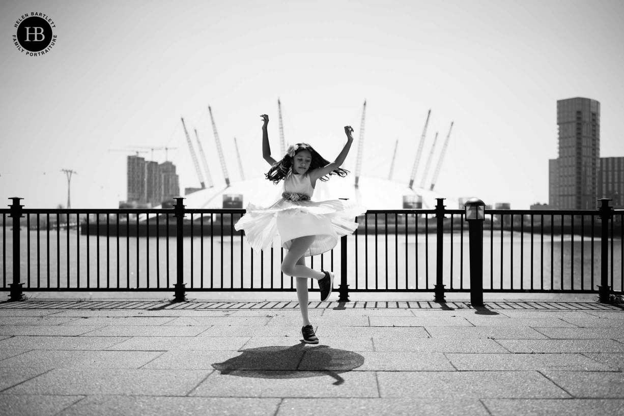 girl dances with O2 arena in the background, her skirt flies out and mirrors the shapes of the Dome