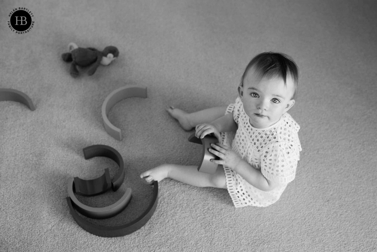 little girl sits on the floor playing with wooden rainbow toys