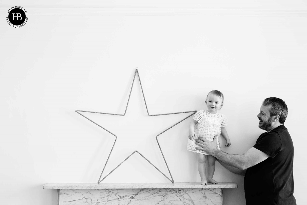 little girl stands on mantlepiece supported by her dad, star decoration