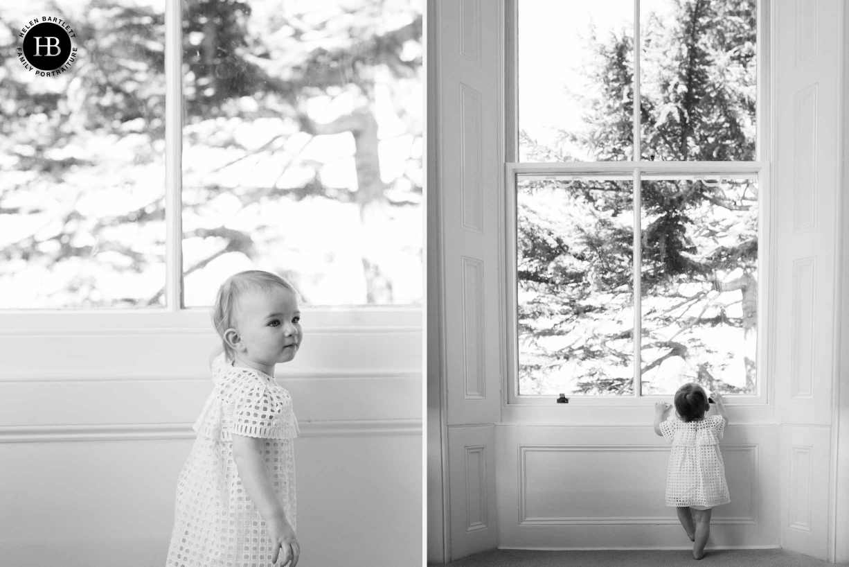 little girl looks out of large sash windows onto trees outside