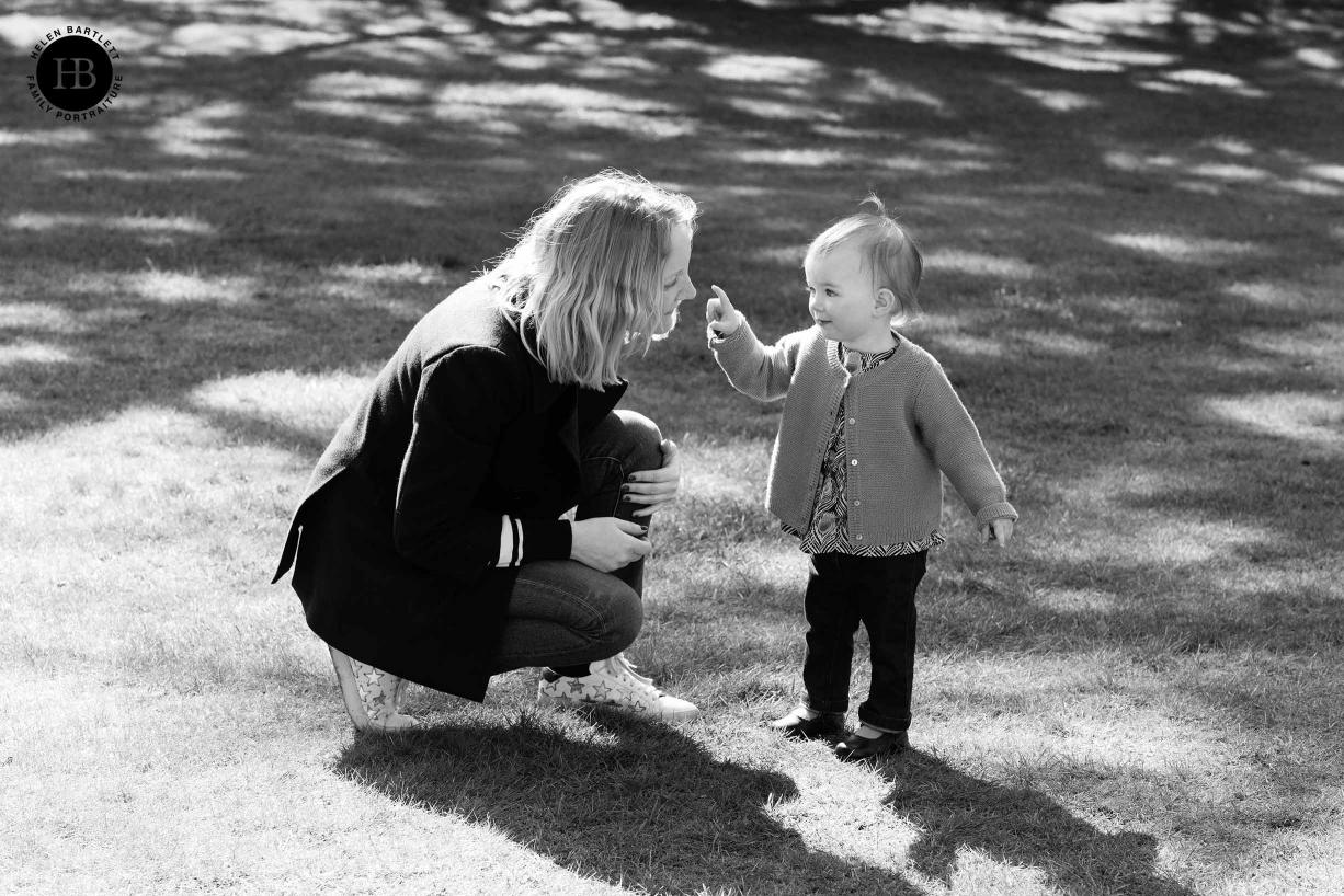 little girl talks to her mum in the dappled sunlight
