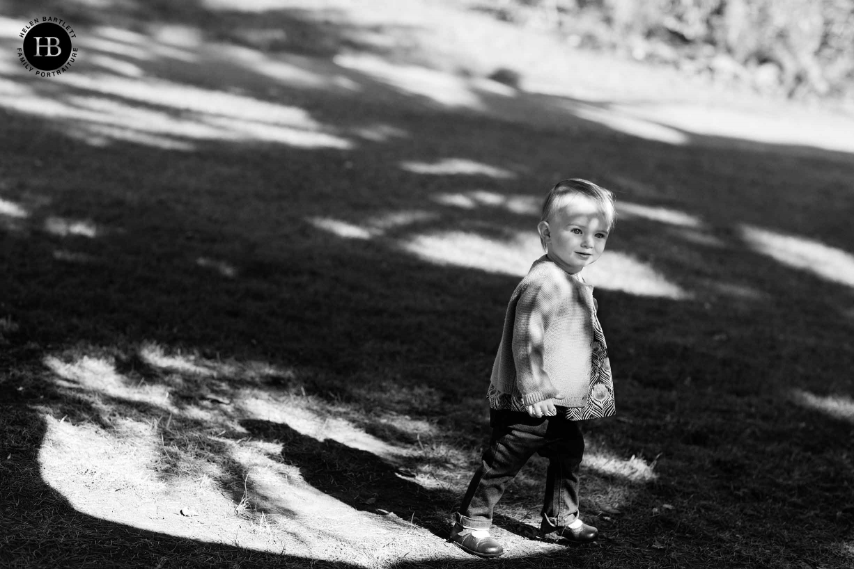 two year old stands in dappled sunlight