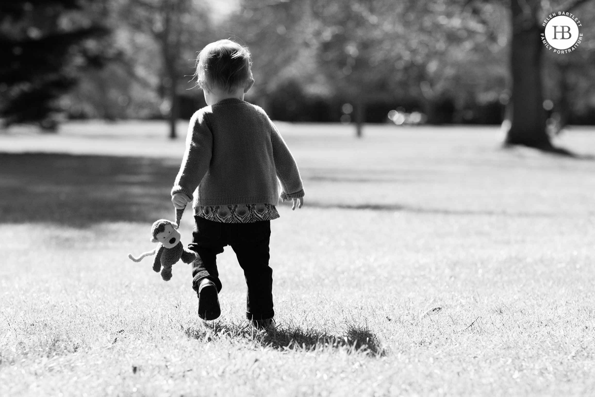 toddler walks away holding toy monkey by the hand on Blackheath