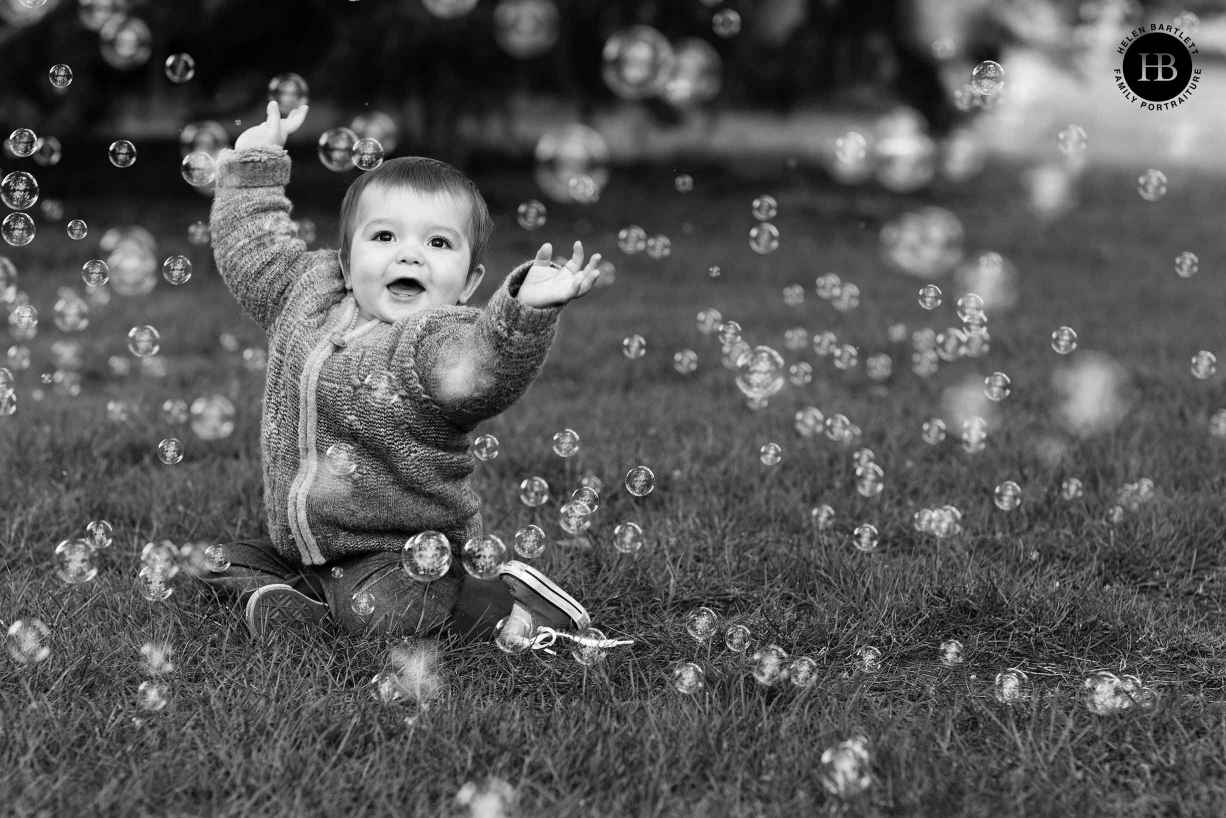 nine month old baby laughs with bubbles in park east london