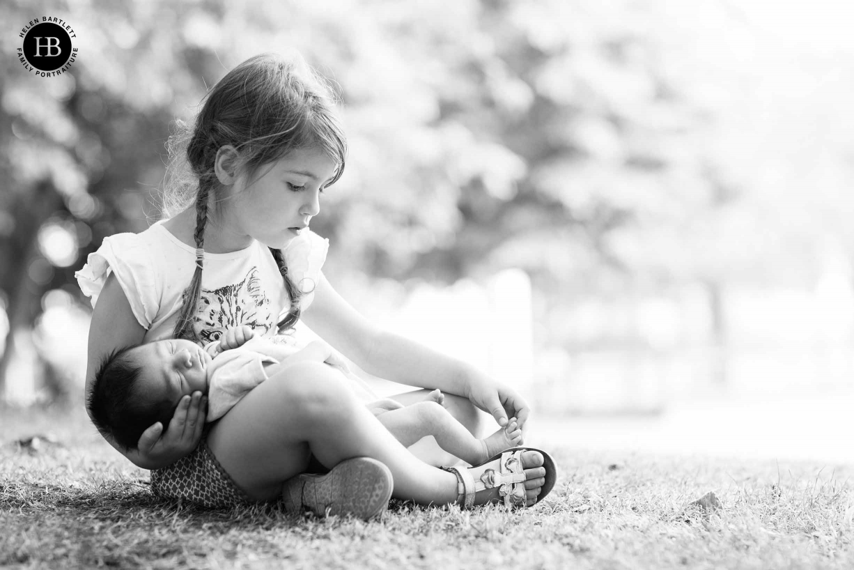 girl plays with newborn brother's toes in park bethnal green east london