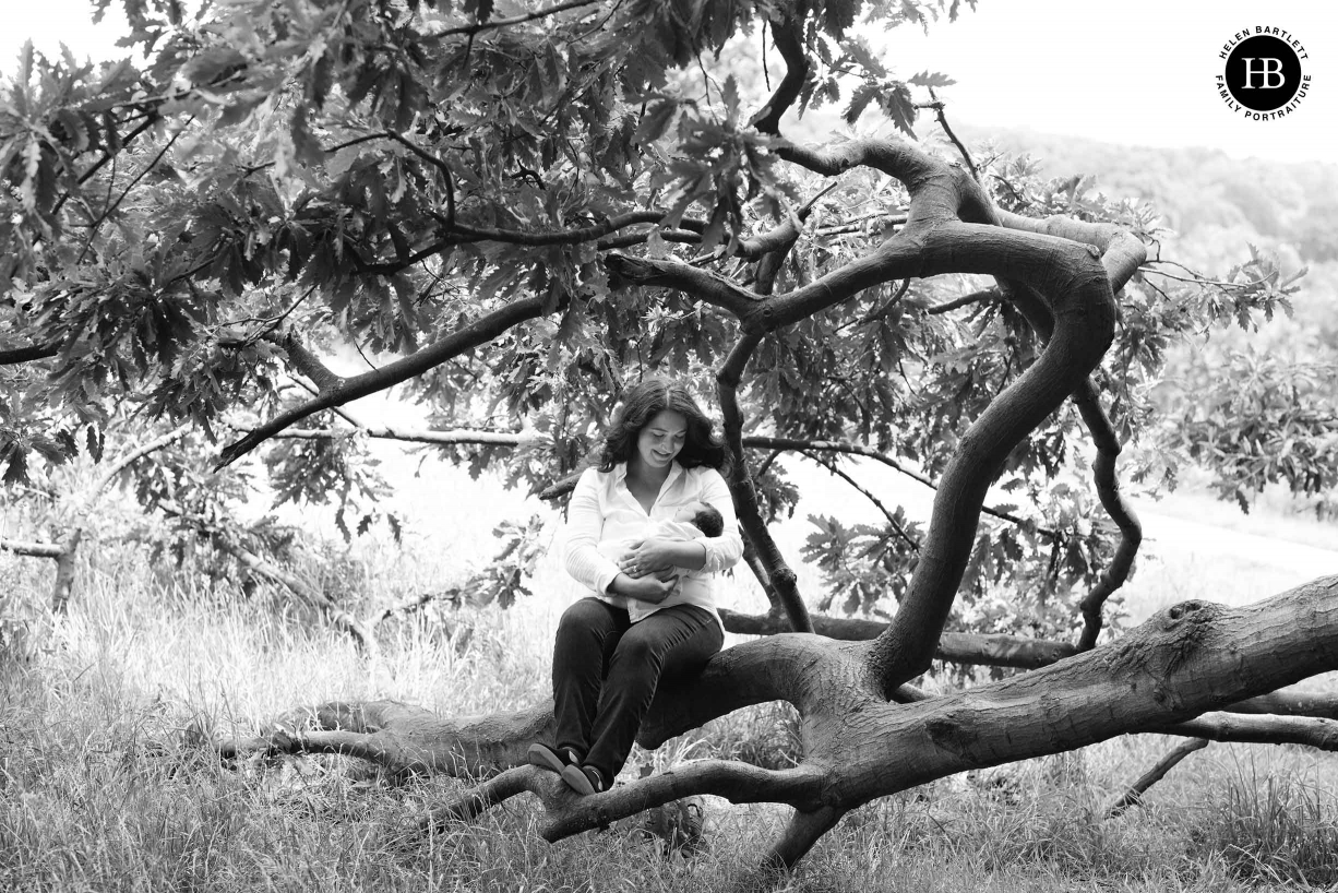 mum sits in tree holding newborn baby