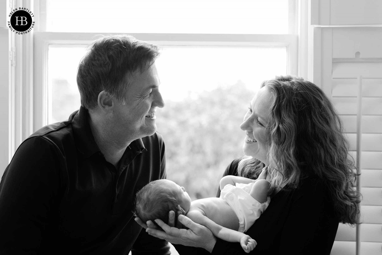 Family photo of mum, dad and newborn in font of window. Parents laughing and happy