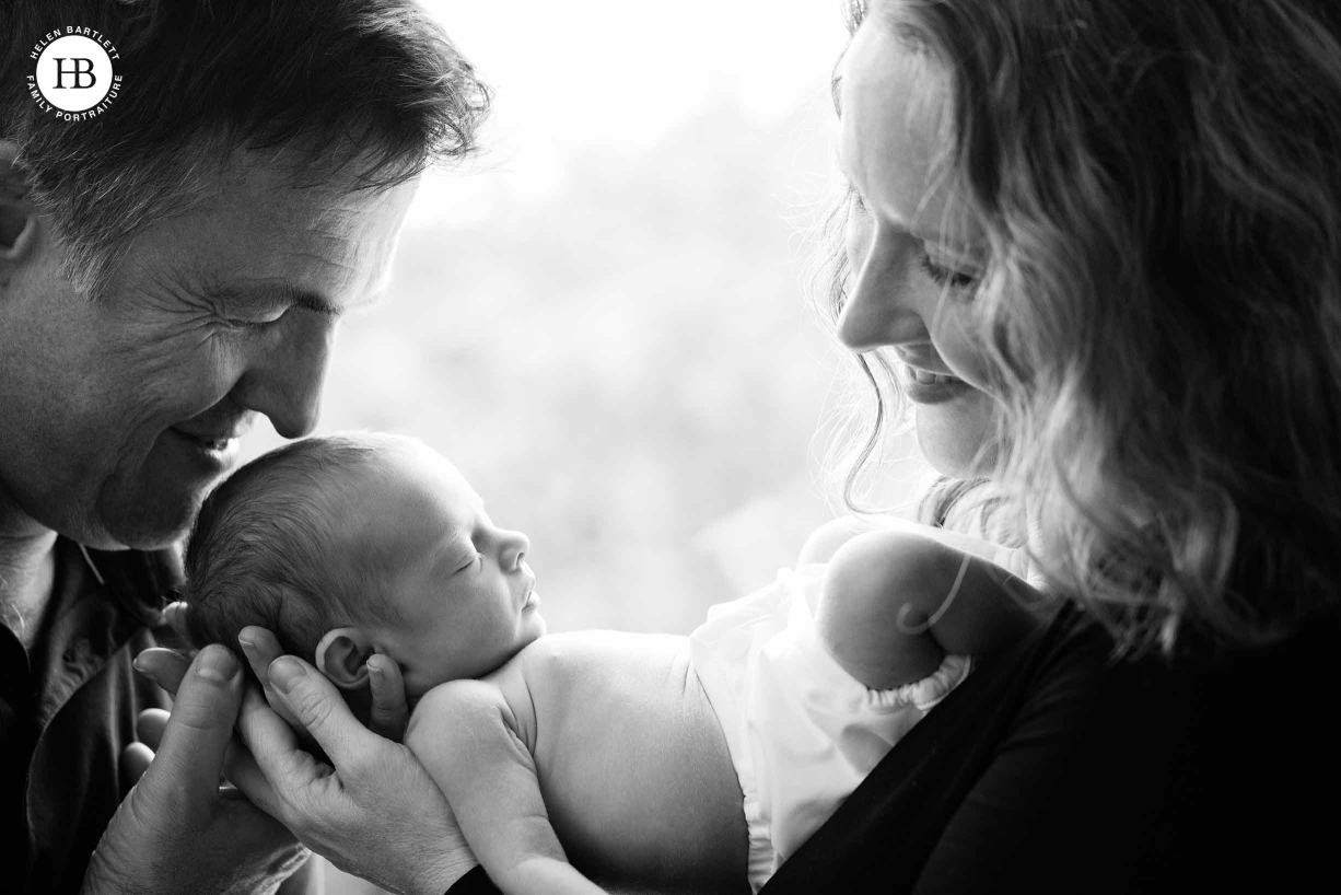Dad kisses baby's head as mum looks on in black and white family photo