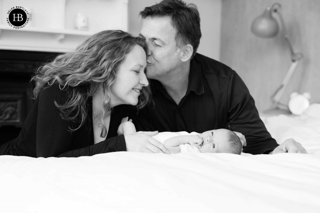 dad kisses mum while baby lies on bed in newborn baby family photoshoot Dulwich