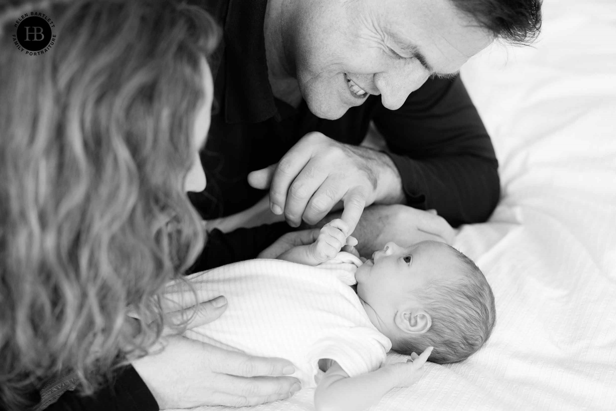 parents look at newborn baby lying on bed, baby holds father's finger
