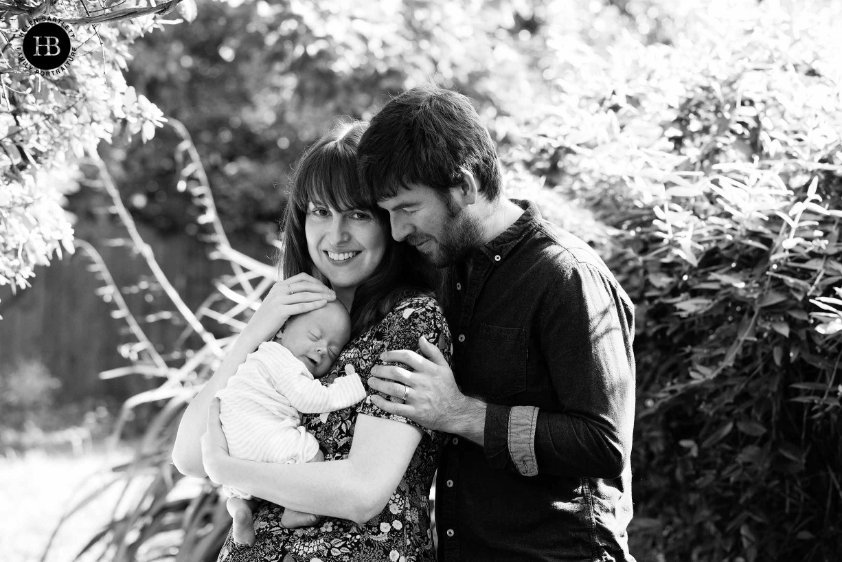 a glorious sunny day, mum and dad hold smiling newborn in the garden