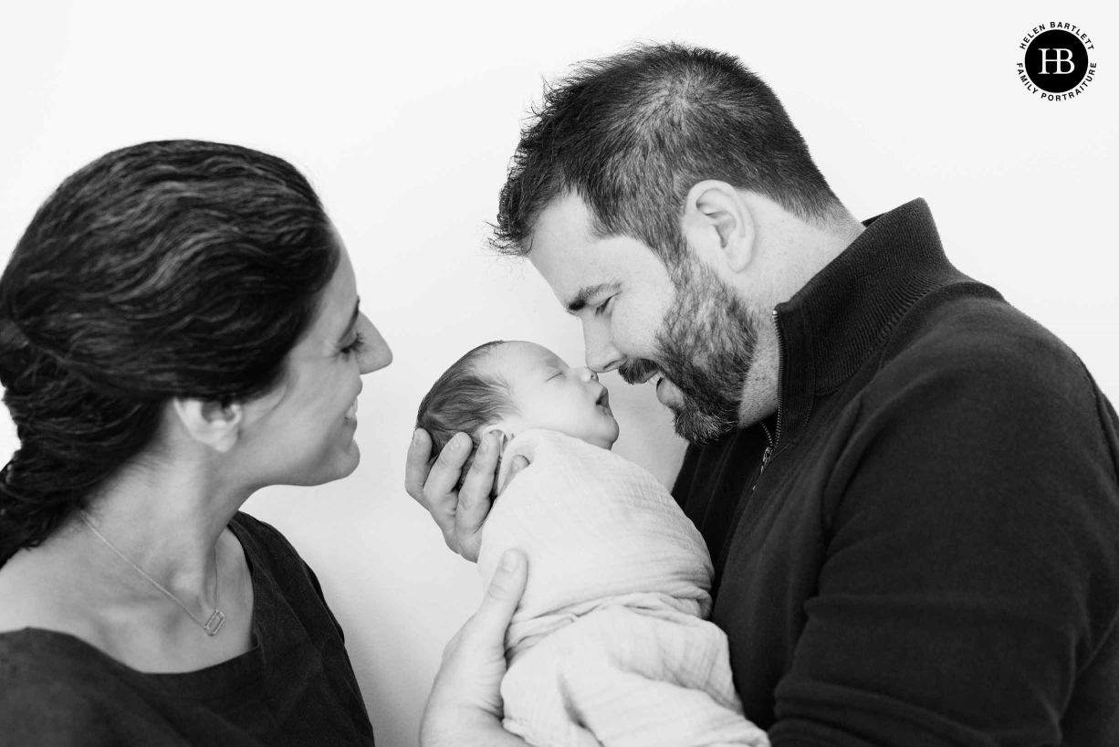 dad touches noses with baby son, mum looks on smiling