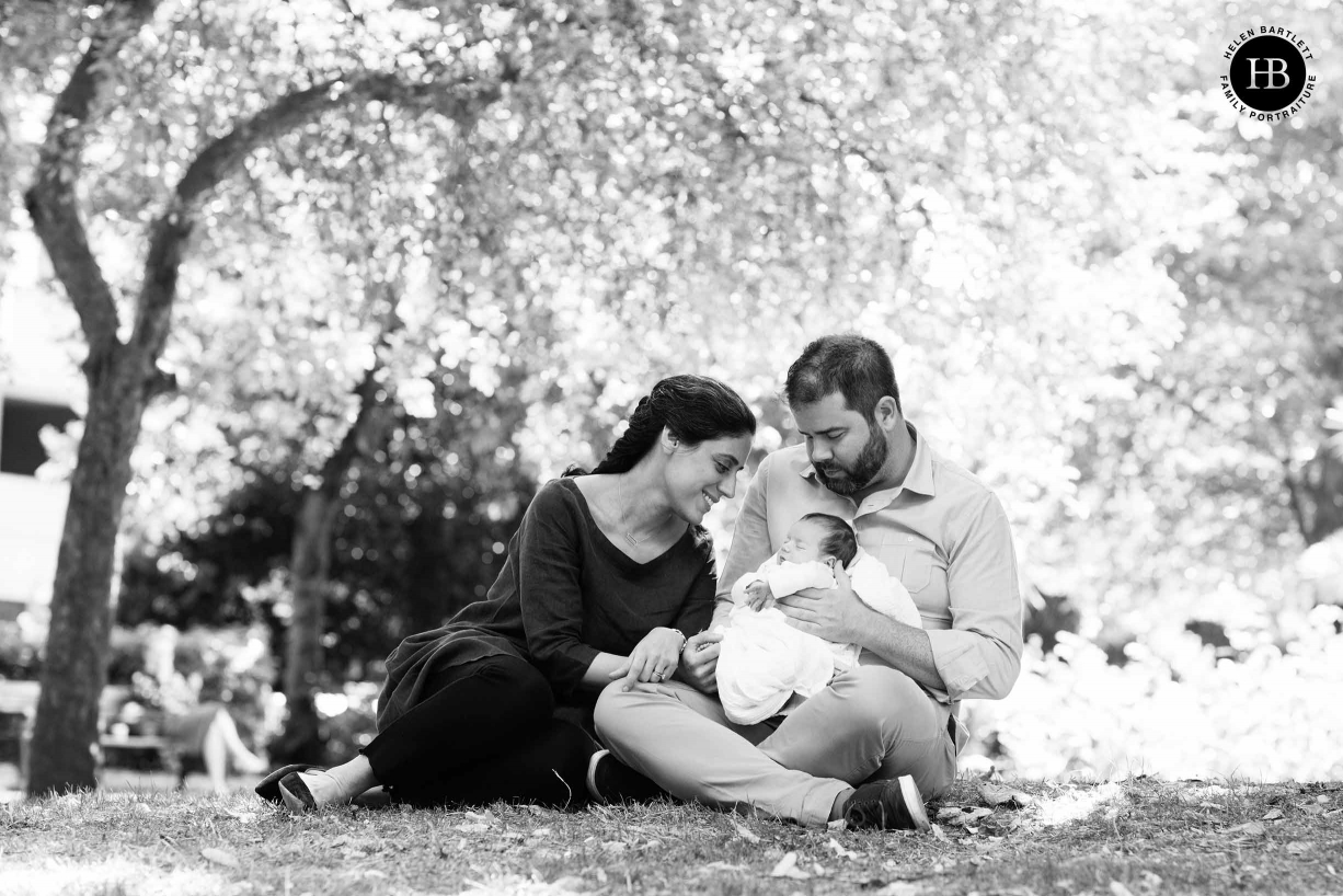 parents and newborn sit under a tree in north london park in spring