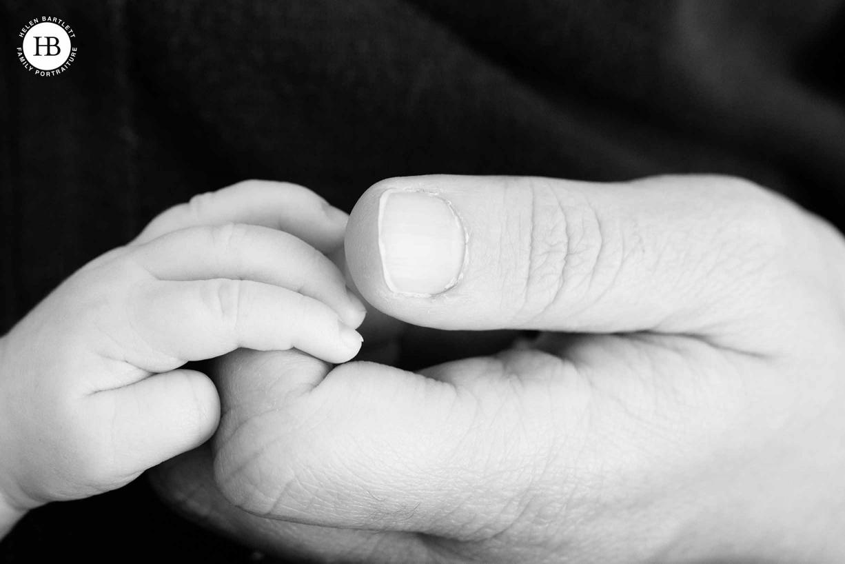 detail shot of dad holding newborn baby son's hand
