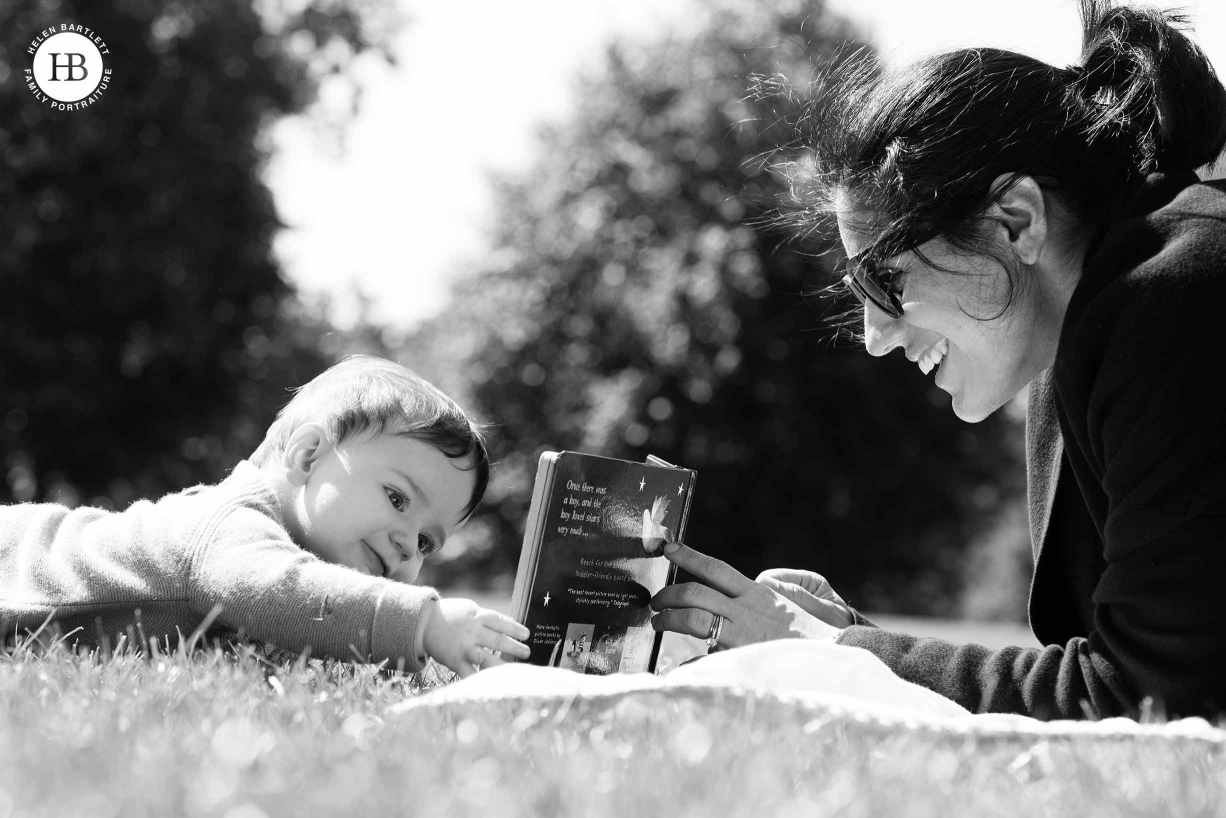 baby and mum read book in the park on summer day