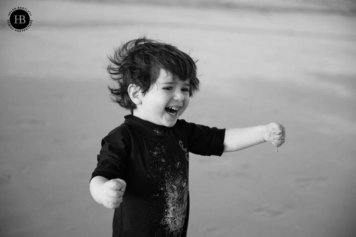small boy plays in the sand on the beach