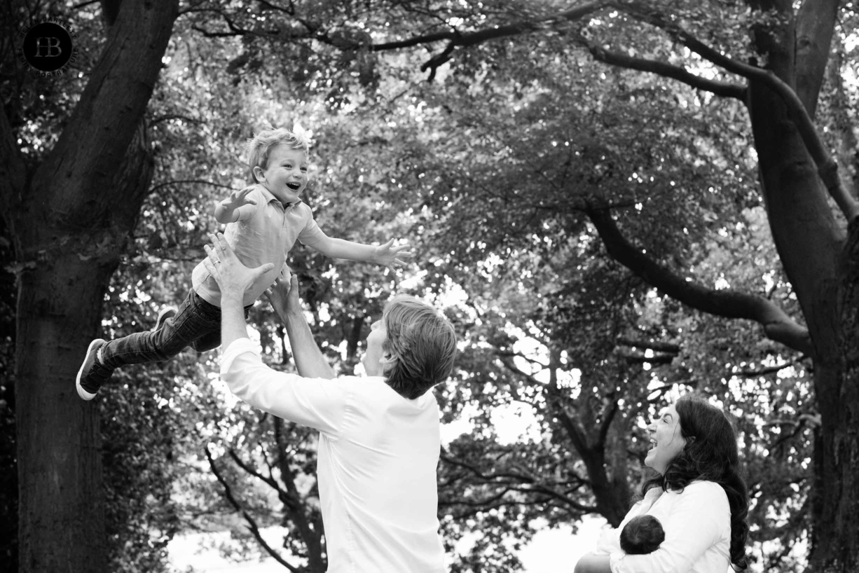 Dad throws son in the air while mum and newborn daughter look on. Fun family photo on Hampstead Heath