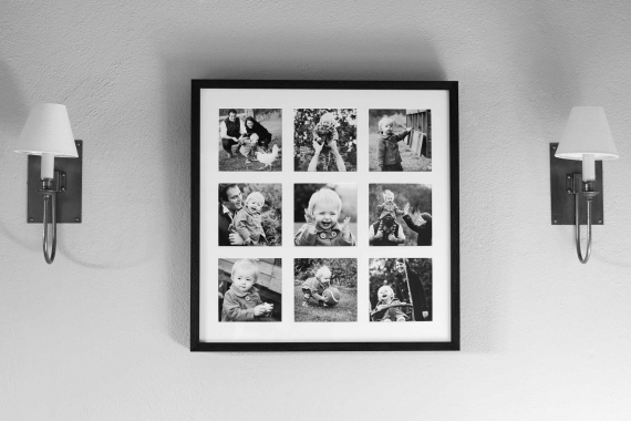 A multi-aperture frame of family portraits shows nine square family portraits in a simple symmetrical arrangement in a classic black frame.
