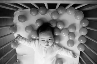A baby lies in its bed surrounded by plastic balls during its baby portraits.