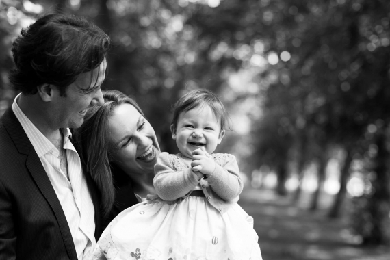 A baby girl claps her hands with her parents during a portrait shoot in classic black and white.