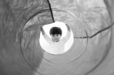 Baby photography: a boy looking down a tunnel in London.