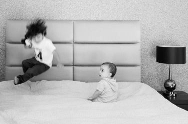 A baby and their older sibling show their energy levels during a baby portrait shoot on a double bed.