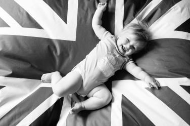 A baby in a onesie bounces on a Union Jack for their portrait shoot in London.