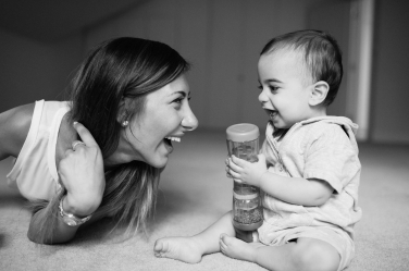 Babies play games during Helen Bartlett's baby portrait shoots. This little one is playing with a shaker and making his mother laugh.