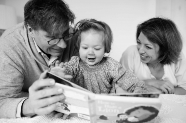 A baby girl and her parents read a book together during their London portrait shoot. Look at their expressions!