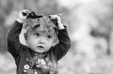 This baby boy makes a leaf into a hat for his autumn portraits.