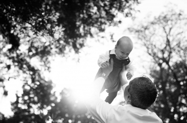 A dad lifts his baby up into the air during a London portrait shoot in black and white.