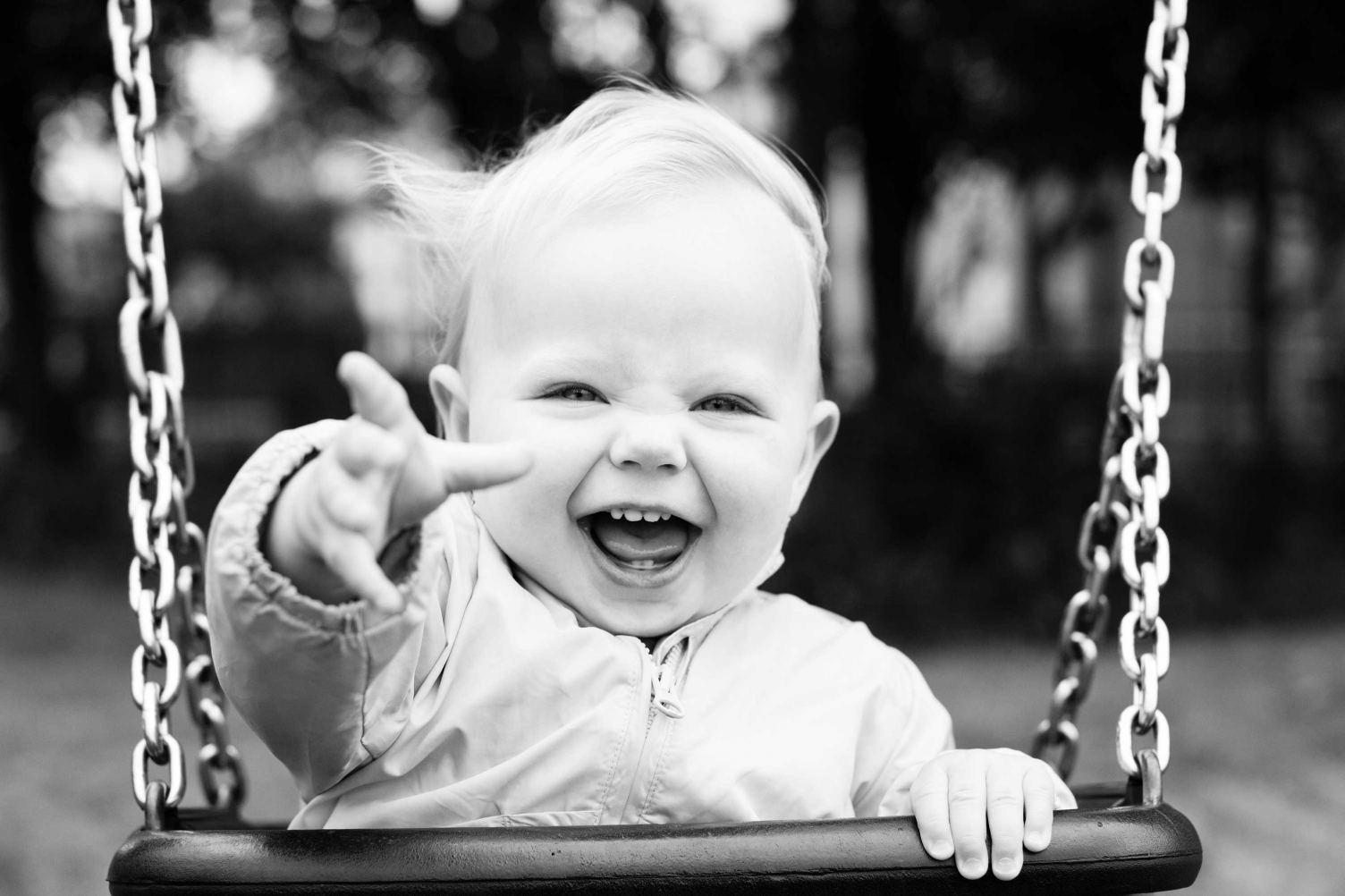 Baby photography: this baby sits in a swing, smiling and pointing at the camera.