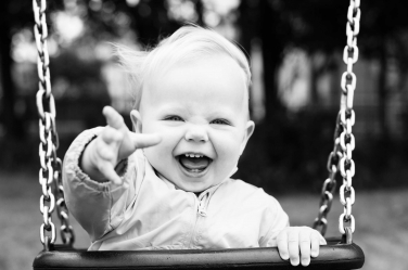 A baby shrieks with delight when on swings in the park during their portrait session.