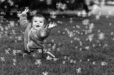 A baby tries to burst all the bubbles during their photo session.