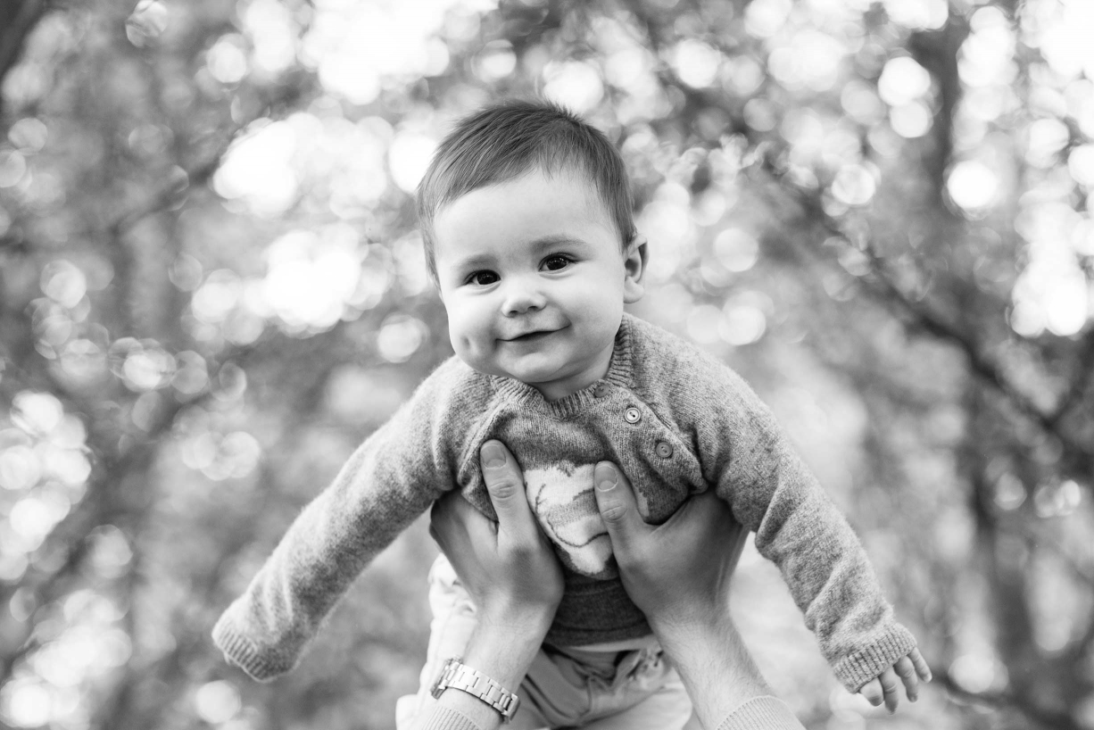 A 'flying' baby is framed by leafy branches in this classic black and white baby portrait.