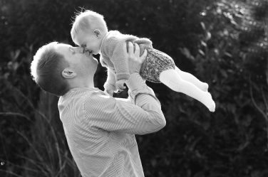 A backlit black and white family portrait shows off the fine blonde hair of this baby girl as her father lifts her in the air and kisses her.