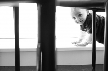 Peekaboo! A baby finds a table and chairs makes a great place for a game during their family portraits.