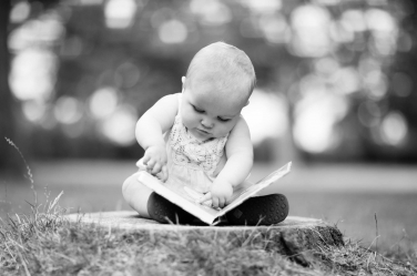 This baby girl looks for all the world as if she is reading her first words, in this black and white professional baby picture.
