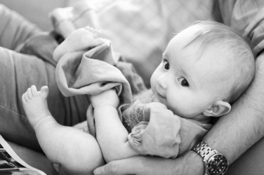 A baby snuggles in her parent's arm - look at those cute pudgy toes!