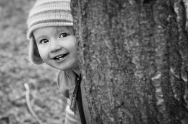 Peekaboo! A little girl looks around a tree in this family portrait shoot.