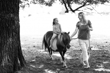 Every little girl's dream - a ride on a pony, led by her mother in these black and white family portraits.
